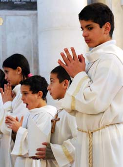 Palestinian children pray in the West Bank City of Ramallah. The October Synod of Bishops for the Middle East will address such things as peace for them, plus issues varying from dialogue among churches to the political status of Christians.