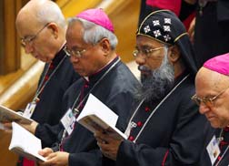Participants follow prayer books at the Synod of Bishops for the Middle East Oct. 11