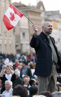 Prior to the canonization Mass a man waves a Canadian flag.