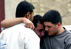 Men mourn outside outside the Syrian Catholic cathedral in Baghdad, Iraq, Nov. 1. Dozens of hostages and police were killed the day before when security forces raided the cathedral to free worshippers being held by gunmen wearing explosives.