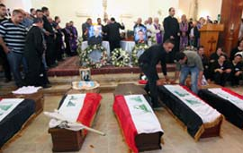 Mourners place Iraqi National flags on coffins during a funeral for Christians killed in an Oct. 31 assault during Mass at the Syrian Catholic Cathedral in Baghdad.
