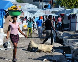 A woman carrying goods walks through the largest tent city of Haitian earthquake survivors.
