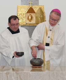 Assisted by Fr. Paul Kavanagh, the archbishop lights incense on the altar.