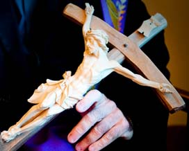 A priest holds a crucifix that he used in performing an exorcism.