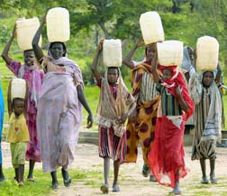 Women carry water drawn from a Darfur well funded by CARITAS and other faith groups.