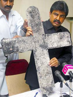 Shahbaz Bhatti shows a cross that was burned during an attack on a church in Pakistan during a news conference in Islamabad in 2005.