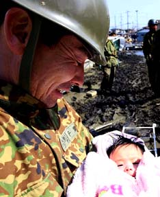 A civil defense officer holds a four-month-old girl who was rescued along with her family from their home in Ishimaki, Japan March 14.