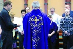 Fr. Andrew Bogdanowicz, pastor of St. Thomas More Parish, leads RCIA catechumens through one of the scrutinies on the Fourth Sunday of Lent, April 3.