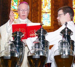 Archbishop Richard Smith blesses the oils at the Chrism Mass April 18 at St. Joseph's Basilica.