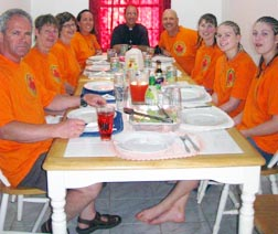 The Holy Trinity team and Hayes Pastor Fr. Francis Dupuis enjoy a meal at the mission house.