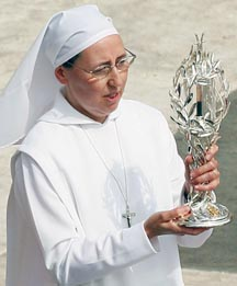Sr. Marie Simon-Pierre, who's cure from Parkinson's disease was accepted as the miracle that paved the way for Pope John Paul II's beatification, carriers a relic of the late pope during his beatification Mass.