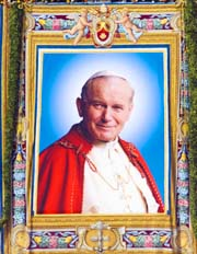 A tapestry bearing a 1995 photo of Pope John Paul II hung from St. Peter's Basilica.