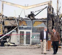 Prime Minister Stephen Harper and Premier Ed Stelmach walk in front of the former town library in Slave Lake May 20. Much of the town was devastated by wildfires May 15 and 16