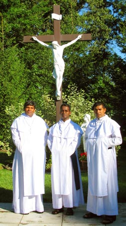 Sri Lankan monks stand by the crucifix at Our Lady of the Rosary Shrine grounds.