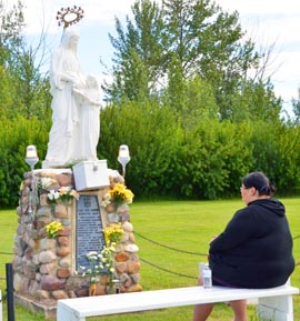 Roberta Beaulieu prays before the statue of St. Anne and the child Mary.