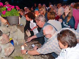 Pilgrims crowd around the top of the grotto to put their candles in place during a procession at the end of Mass.
