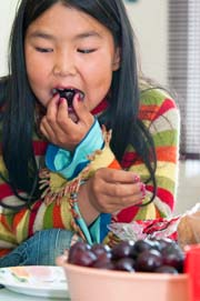 Kedra Kimiksana tastes cherries for the first time at Sr. Fay's house.