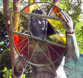 A three-metre bronzed sculpture depicts a sister holding a huge piece of stained glass that symbolically depicts the breadth and depth of the sisters' service to the province of Alberta.