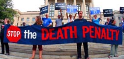 People hold a banner and signs on the steps of the Georgia Capitol in Atlanta during a vigil for inmate Troy Davis before Sept. 21 execution.