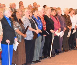 People attending the Strathcona County Ecumenical Mission stand together to join in song.