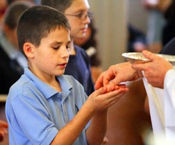 A young student receives Communion during a school Mass underlining the importance of promoting Catholic identity in Catholic high schools and elementary schools.