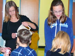 St. Martin Students Lesia Bogdan and Maria Ovcharenko give 'hungry snacks' to younger pupils. The snack consisted of water and a soda cracker.