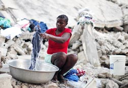 A woman washes clothes in Port-au-Prince early this year next to a house destroyed by the Jan. 12, 2010 earthquake that devastated Haiti.