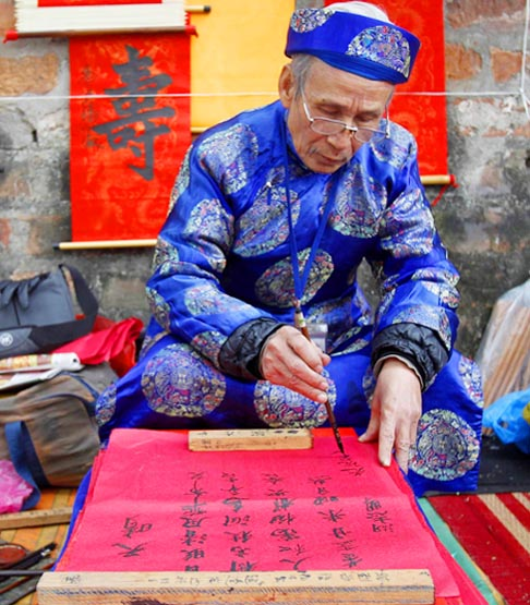 A calligrapher paints while waiting for customers on a street in Hanoi, Vietnam, Jan. 13. Calligraphy paintings are used for decoration during Tet, the Vietnamese lunar new year, which began Jan. 23.