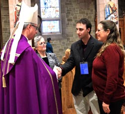 Matthew Kellert of Olds is joined by his wife Shaleen in being greeted by Archbishop Richard Smith at the Rite of Election Feb. 26 at St. Joseph's Basilica while Susan Barylo observes.
