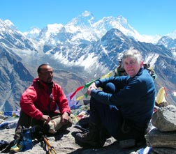 Mary Martin and friend Mukhiya take a break on Gokyo and enjoy the sight of Mt Everest in the background.