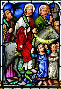 A church window depicts Christ's triumphal entry into Jerusalem before his crucifixion.