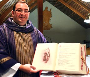 Fr. Paul Kavanagh shows some of artwork contained in the new missal.