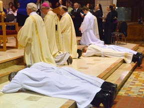 The four diaconal candidates lay prostrate in the sanctuary prior to their ordination by Archbishop Richard Smith June 2 at St. Joseph's Basilica.