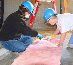 Claire Rolheiser, left, and Sr. Mary Clare Stack measure out insulation batting for a new Habitat house.