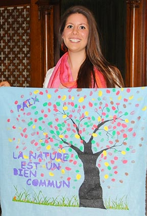 Janelle de Rocquigny stands with her solidarity banner, painted by the youth of St. Boniface Cathedral in Winnipeg before departing for Rio de Janeiro.