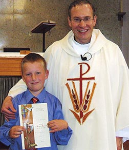 Fr. Greg Bittman is seen with his nephew Brad after giving him First Communion.