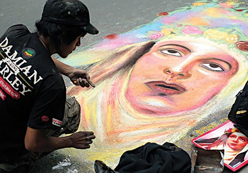 A man draws an image of St. Rose of Lima in chalk on a street in Lima, Peru, Aug. 30. She is patroness of Peru and the first named saint from the Americas.