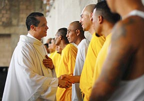 Bishop Fabio Colindres Abarca shakes hands with members of a gang during a Mass at the prison of Izalco near San Salvador