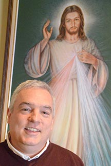 Dr. Robert Stackpole stands before an image of Jesus, the Divine Mercy.