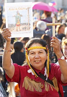 An aboriginal woman holds up an image of St. Kateri Tekakwitha in St. Peter's Square.