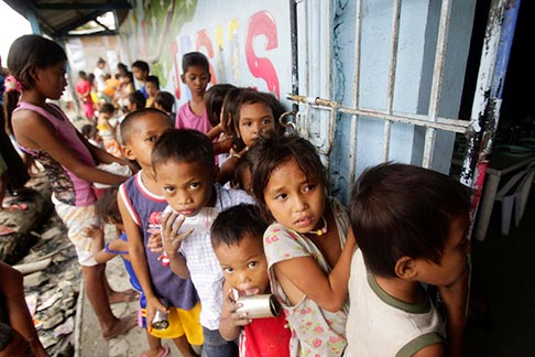 Children living in a squatters' area wait Sept. 21 for a free meal consisting of rice, chicken and vegetables that is given out daily by a South Korean religious missionary organization near Manila, Philippines.