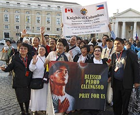 Pilgrims from the Edmonton Archdiocese, including Fr. Nilo Macapinlac (right), carry a banner honouring St. Peter Calungsod, a lay catechist from the Philippines who was martyred in 1672, as they arrive for the canonization Mass in St. Peter's Square at the Vatican Oct. 21.