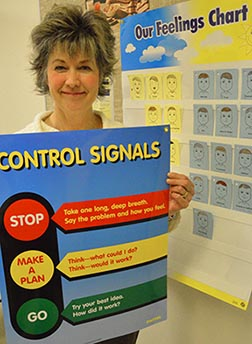 Grade 3 teacher Carolyn Guterson holds up a Control Signals poster that is on display at several places in Our Lady of the Prairies School.
