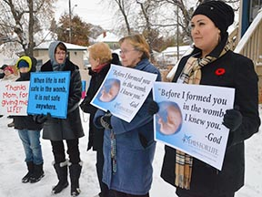 April Madden, right, is joined by her son Myles, left, and women from Camrose in praying across the street from the abortion clinic for the lives of the unborn.
