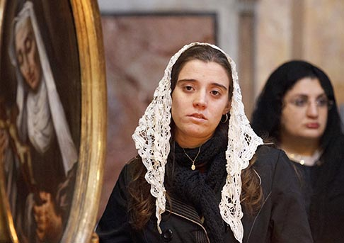 Maria Regina Zucchi, 24, of Sao Paolo, Brazil, stands near a painting of a saint as she attends a Mass at the Church of the Holy Trinity of the Pilgrims in Rome Nov. 1, the feast of All Saints.