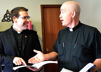 Deacon Matthew Hysell (left), who will be ordained a priest Dec. 7, discusses a point with Fr. Jim Corrigan, pastor of Edmonton's St. Theresa Parish.