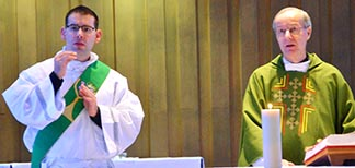 Deacon Matthew Hysell (left) translates the Mass into sign language at a Nov. 18 Mass for the deaf celebrated by Fr. Ray Sevigny (right).