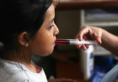 A nurse uses a syringe to give liquid medicine to a young HIV patient at San Jose Hospice in Sacatepequez, Guatemala. Pope Benedict XVI, speaking about World AIDS Day Dec. 1, said his thoughts and prayers were with