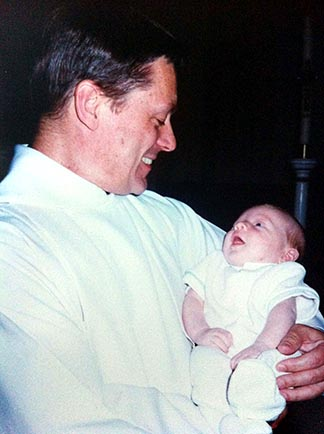 Fr. Paul Terrio holds Chad Brenneis following the baby's Baptism in August 1996.
