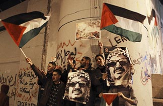 Palestinians hold posters with an image of the late Palestinian leader Yasser Arafat and wave flags as the UN General Assembly granted Palestine observer status.